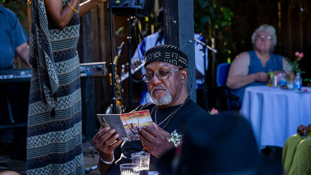 cd release performance- pic of audience member reading cd notes