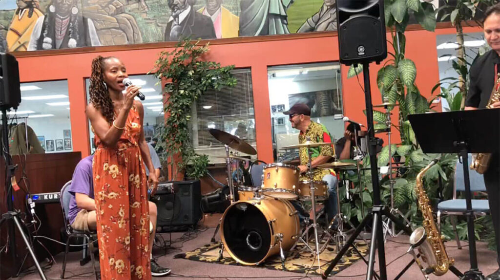 african marketplace 2019 - full shot of sabrina singing with drums and sax